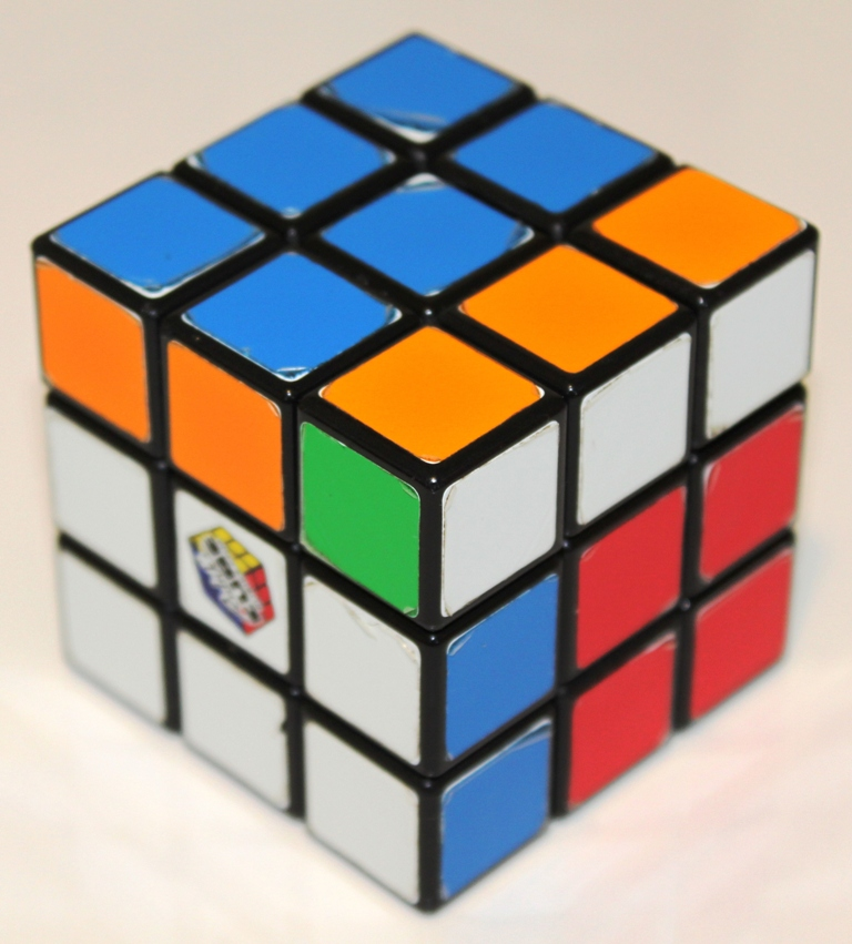 Rubiks Cube, nearly solved. Five edges are solved, six are one quarter turn from solved, and one is two quarter turns from solved — a sum of eight.